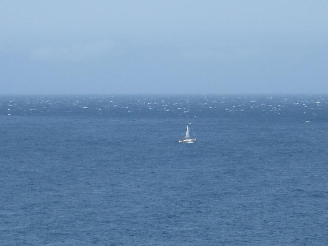 Ein kaum zu erkennendes Segelboot in weiter Ferne